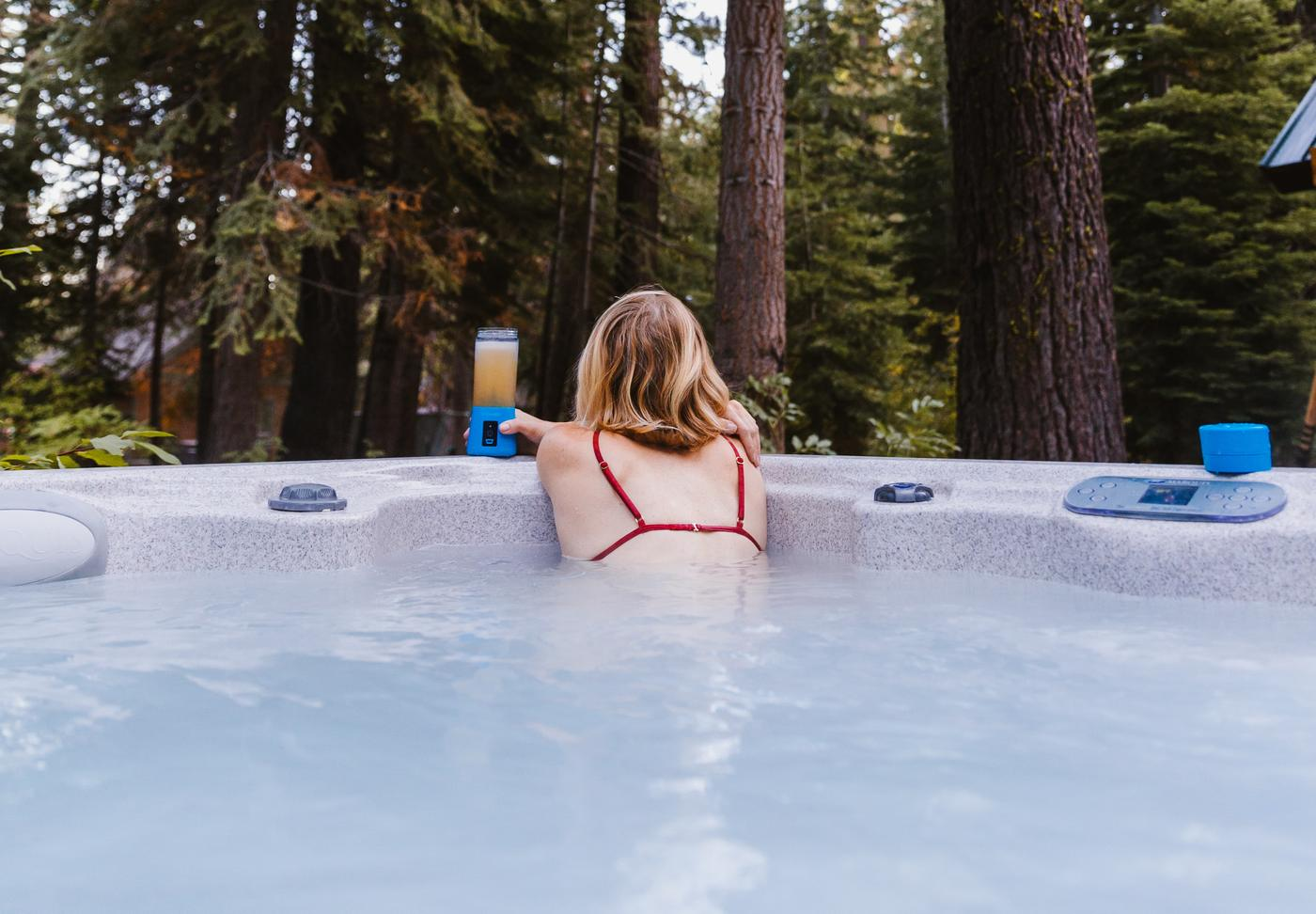 woman on the side of a hot tub looking into a forest